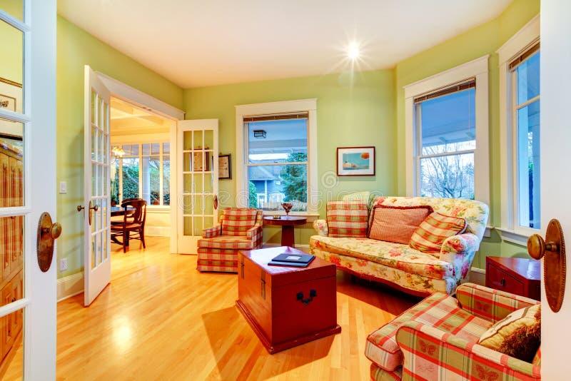 Sala de visitas luxuosa verde-clara dourada com sofás vermelhos. imagem de stock royalty free