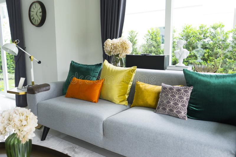 Sala de visitas moderna com sofá cinzento e os descansos coloridos foto de stock