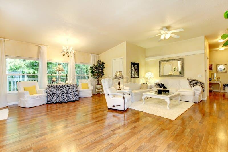 Sala de visitas surpreendente com mobília branca e o assoalho de madeira duro imagens de stock