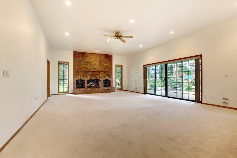 Sala de visitas vazia muito grande com chaminé do tijolo. fotografia de stock royalty free