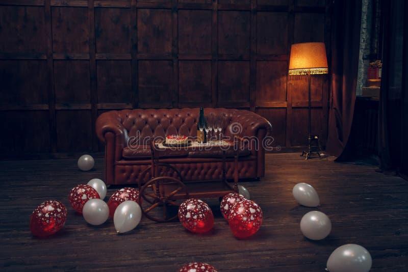 Sala decorada do aniversário com o bolo no trole e nos balões foto de stock royalty free
