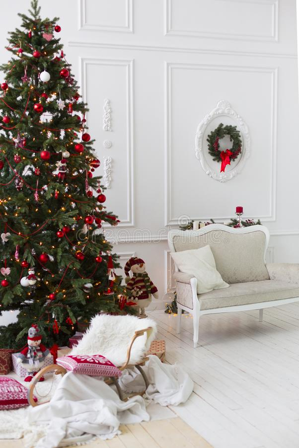 Sala do Natal ou do ano novo com a árvore de Natal vestida com as bolas do Natal e velas vermelhas, trenó de madeira decorativo c imagem de stock royalty free