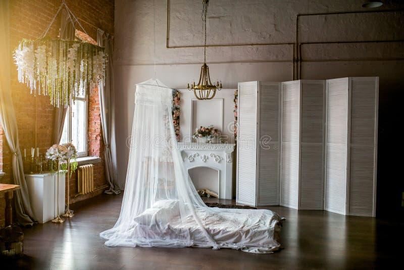 sala do Sótão-estilo com uma cama, um dossel, uma chaminé branca com um arranjo de flor, uma tela branca, um candelabro da flor e fotos de stock