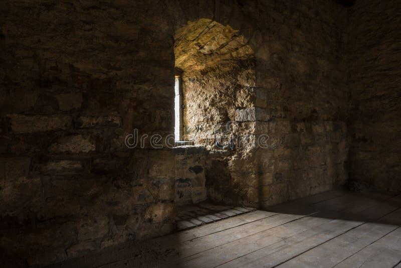 Sala escura com a janela das paredes de pedra e a escadaria de madeira foto de stock royalty free