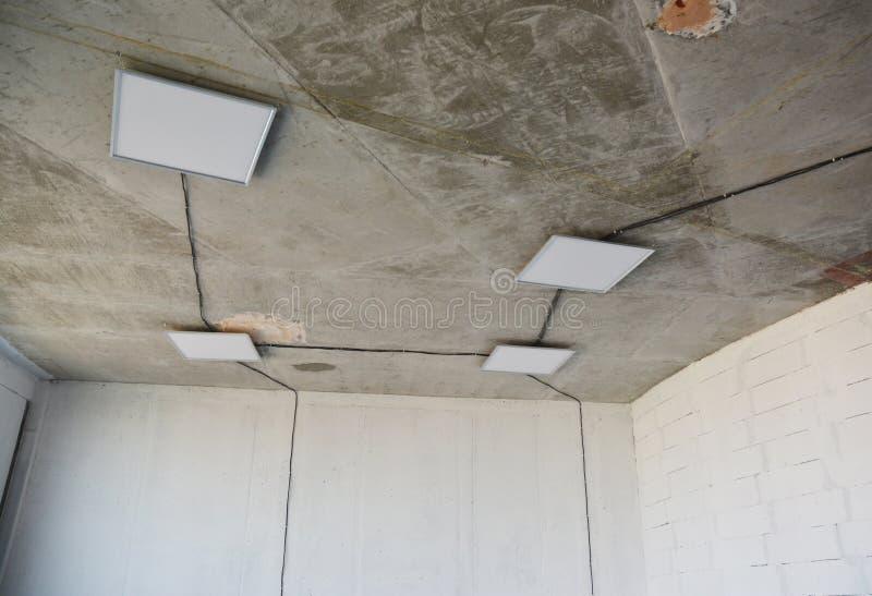 Sala incompleta com lâmpadas de projeto de fôlego de raios quadrados no teto e fiação elétrica instalada no teto sem estacas foto de stock