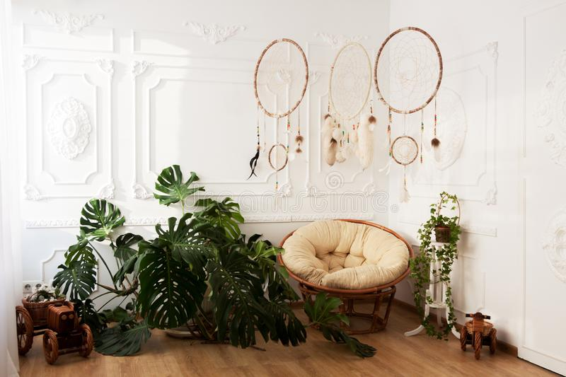 Sala interior com o monstera tropical dos houseplants, os dreamcatchers e a cadeira papasan imagens de stock royalty free