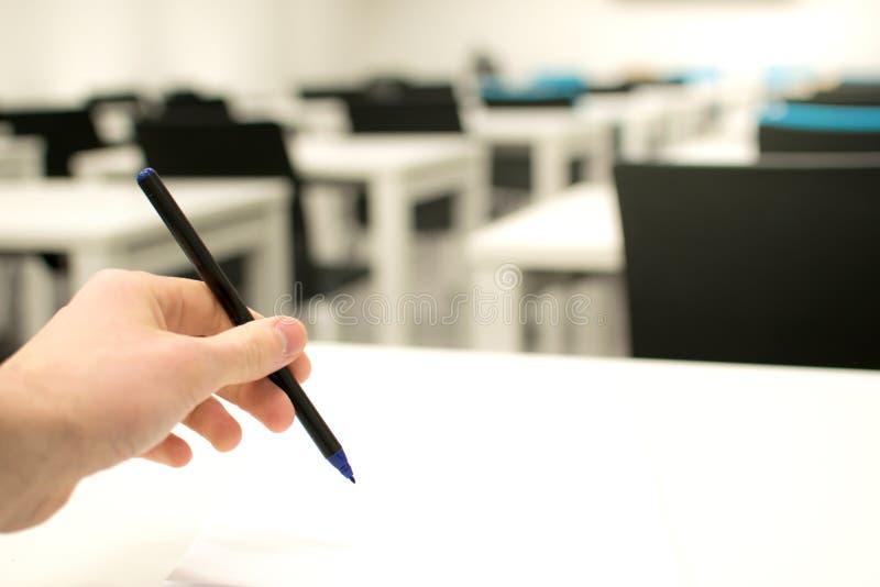 Sala lekcyjna pusta Szkoły średniej lub student uniwersytetu mienia pióro pisze na papierowym odpowiedzi prześcieradle obraz royalty free