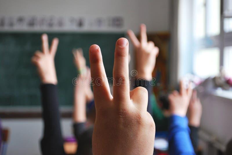 Sala lekcyjna uczni ręki podnosić obrazy stock