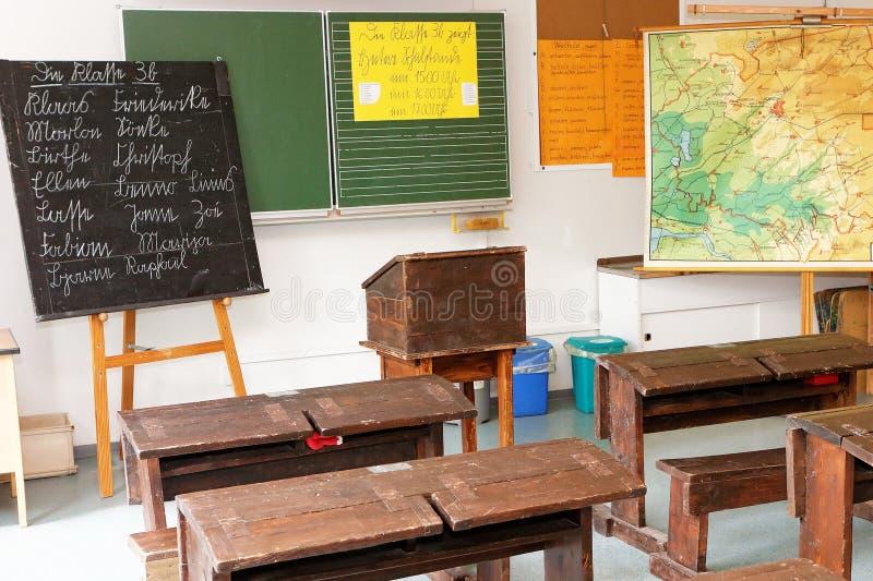 Sala lekcyjna z starymi biurkami, deską i mapą, zdjęcie royalty free