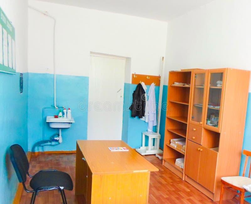 Sala médica na escola com uma bacia da tabela e de lavagem do armário paredes azuis e brancas, vestidos médicos no gancho fotografia de stock royalty free