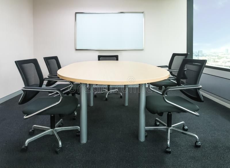 A sala metting tem a mesa de madeira e cadeiras pretas Meettin do escritório fotografia de stock royalty free