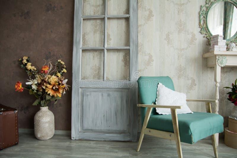 Sala retro interior com uma poltrona, as flores, a porta e o espelho fotografia de stock royalty free