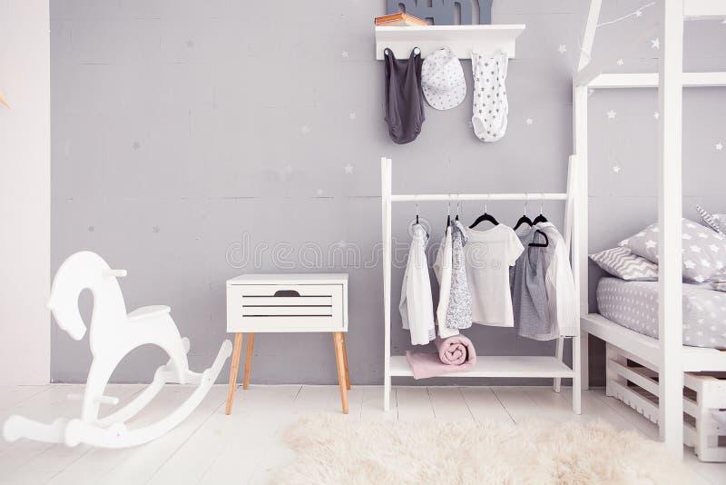 Sala vazia do berçário com parede clara, brinquedos e o cavalo de madeira fotografia de stock