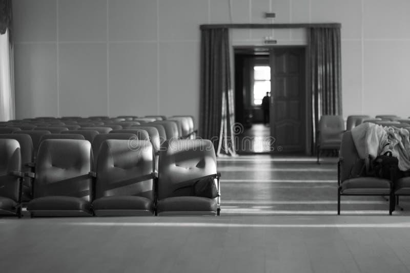 Sala vuota con la foto in bianco e nero beige delle sedie, del teatro o della sala per conferenze fotografia stock
