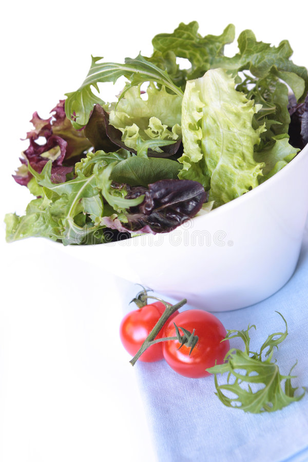 Salad. With mixed lettuce leaves and cherry truss tomatoes. White bowl on pastel blue napkin royalty free stock photos