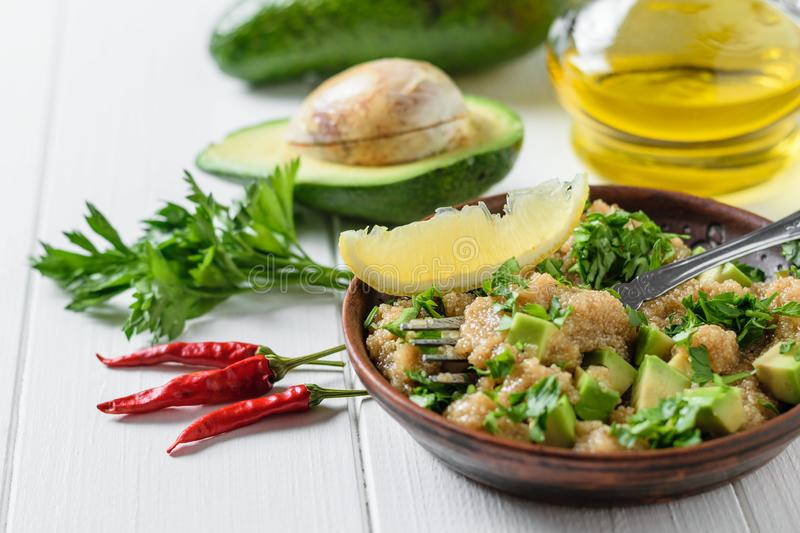 Salad of amaranth seeds, avocado, pepper, lemon and parsley with olive oil on a white table. Dietary vegetarian dish stock photos