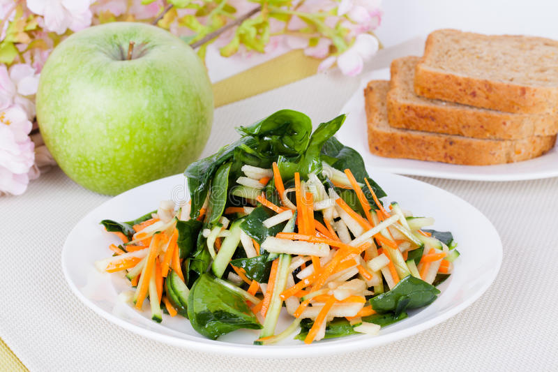 Salad with apple and carrot. On a plate in a still life royalty free stock image