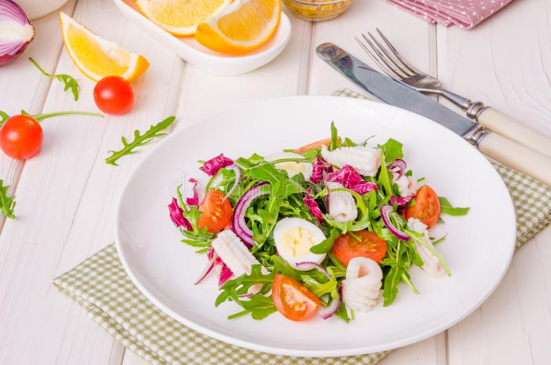 Salad with arugula, squid, cherry tomatoes, onion and quail eggs royalty free stock image