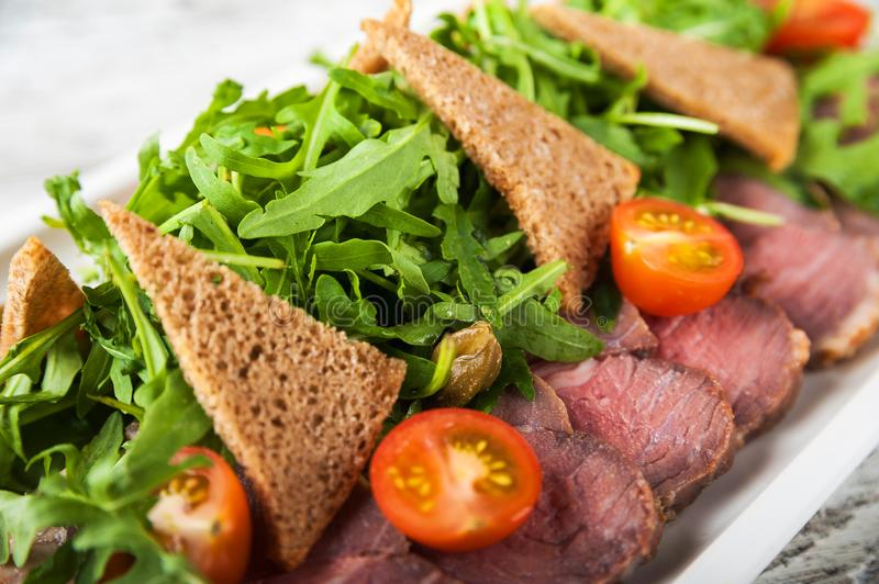 Salad from arugula and tomatoes. Slices of chopped bread and sliced meat. Close-up on a white plate stock photo