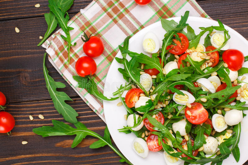 Salad with arugula on a wooden background. Salad with arugula, cherry tomatoes, mozzarella, quail eggs and pine nuts on a wooden background stock photos