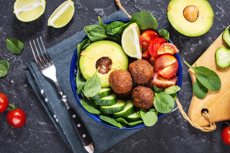 Salad with avocado, falafel, cucumber, cherry tomato and spinach on black stone background. Healthy vegan lunch bowl stock image