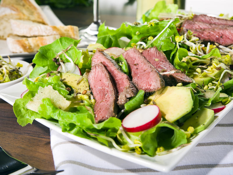 Salad with avocado, radish, ginger, sprouts, beef stock images