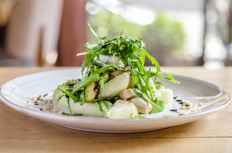 Salad of bananas and herbs on a white plate, on a wooden table royalty free stock photography