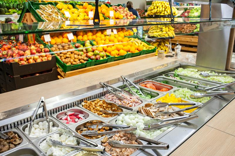 Salad bar on the background of shelves with vegetables and fruits in supermarket stock images
