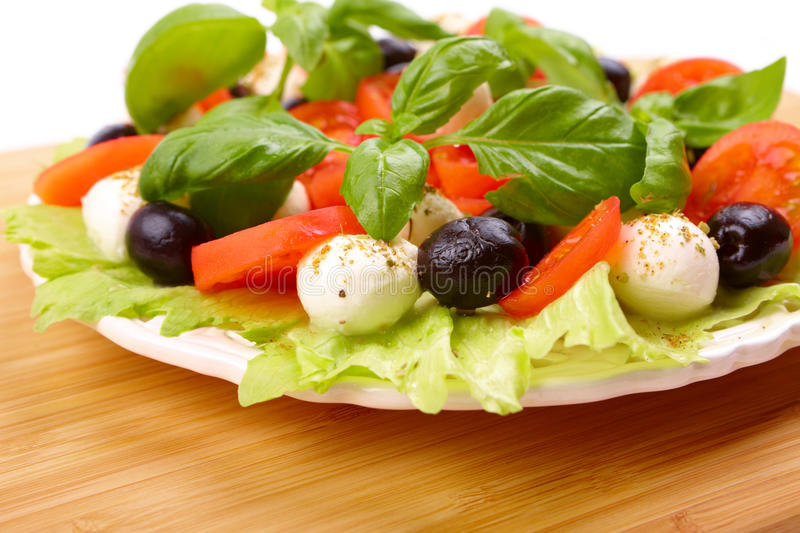 Salad with basil, mozzarella, olives and tomato royalty free stock images
