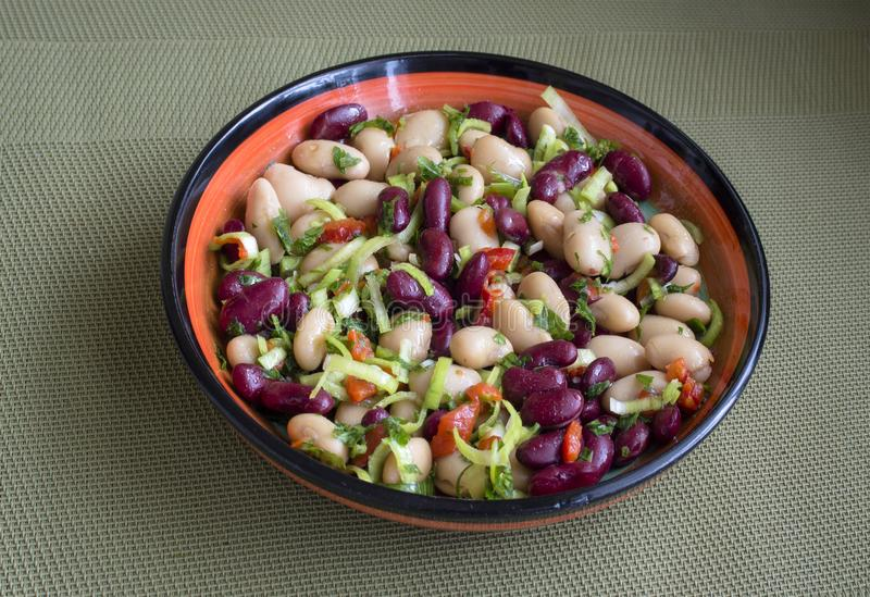 Salad of beans in a colorful dish on a green background. stock photos