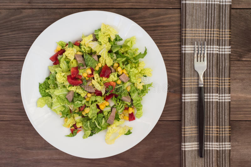 Salad from beef tongue, Chinese cabbage, peppers, corn, parsley and basil. Wooden background. Top view royalty free stock photos