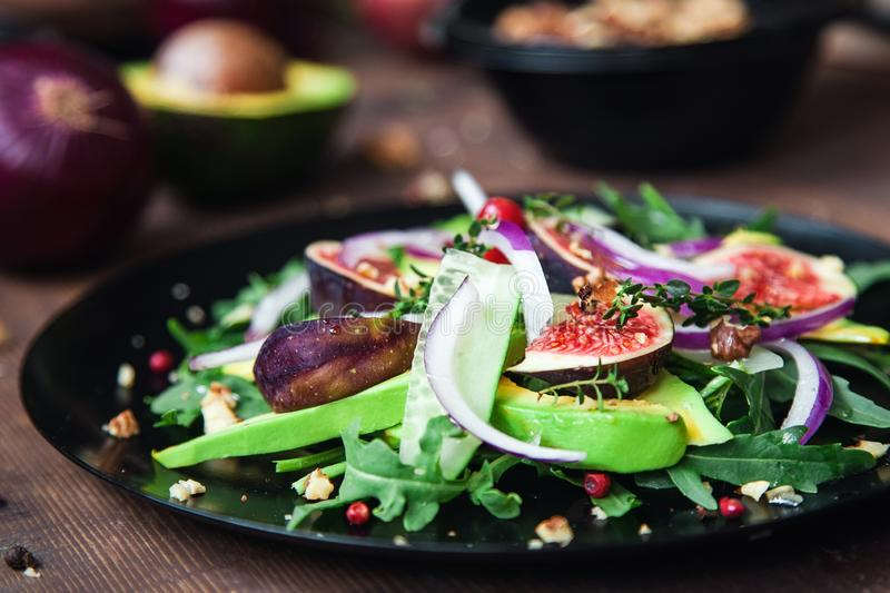 Salad on a black plate: arugula, figs, avocado, red onions, cucumbers, walnuts, viburnum, thyme, spices stock photography