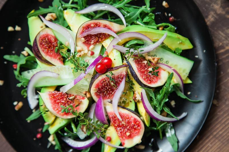 Salad on a black matte plate: arugula, figs, avocado, red onions, cucumbers, walnuts, viburnum, thyme, spices royalty free stock photography