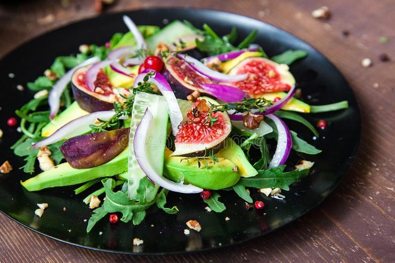 Salad on a black matte plate: arugula, figs, avocado, red onions, cucumbers, walnuts, viburnum, thyme, spices royalty free stock image