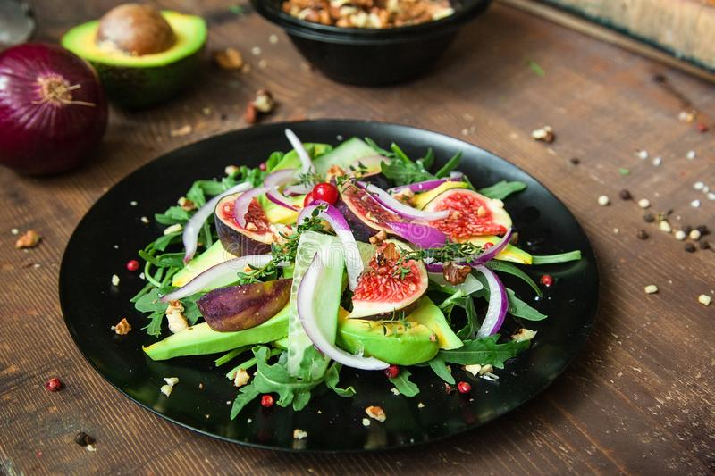Salad on a black matte plate: arugula, figs, avocado, red onions, cucumbers, walnuts, viburnum, thyme, spices stock images