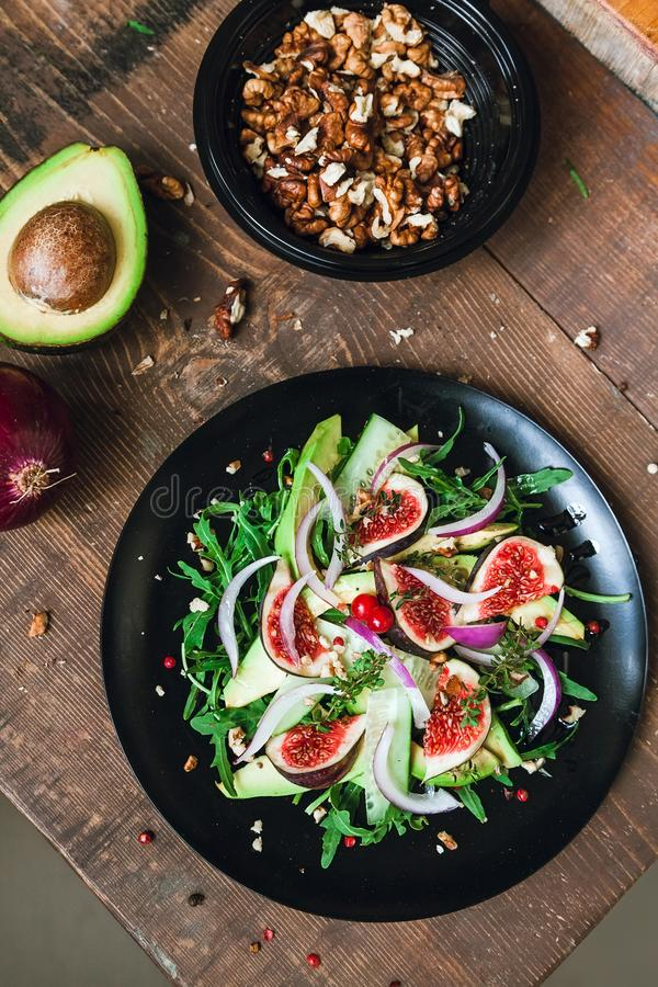 Salad on a black plate: arugula, figs, avocado, red onions, cucumbers, walnuts, viburnum, thyme, spices royalty free stock image