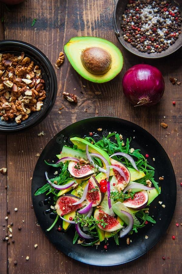 Salad on a black plate: arugula, figs, avocado, red onions, cucumbers, walnuts, viburnum, thyme stock photo