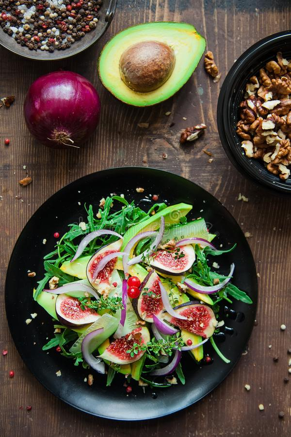 salad on a black plate: arugula, figs, avocado, red onions, cucumbers, walnuts, viburnum, thyme royalty free stock image