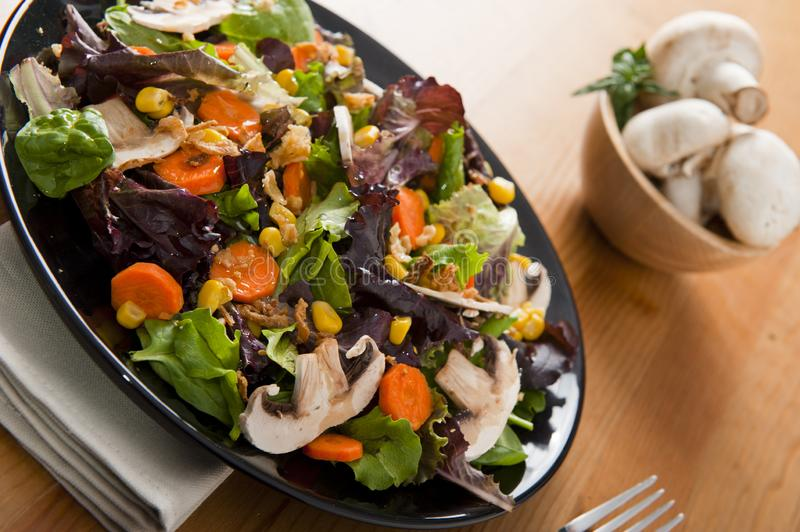 Salad. On black plate over napkin on the table stock images