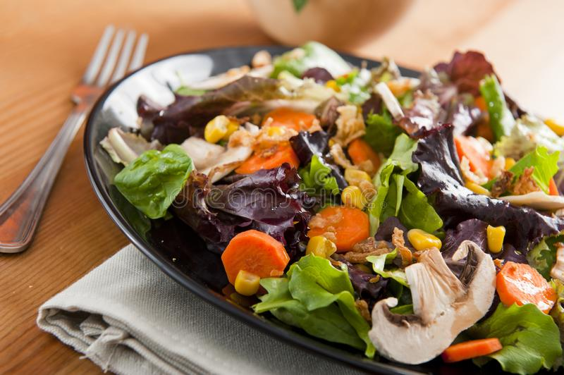 Salad. On black plate over napkin on the table royalty free stock photos