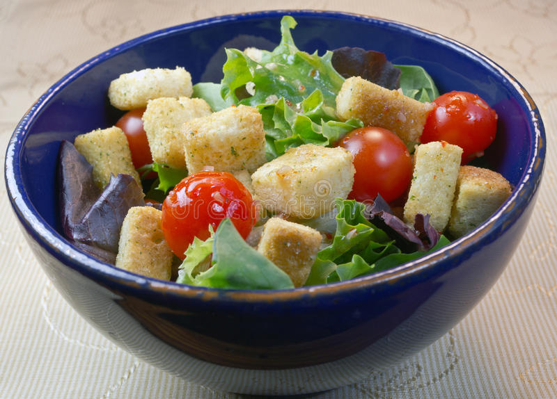 Salad in a blue bowl. And on a textile with assorted greens, croutons, tomatoes royalty free stock photos