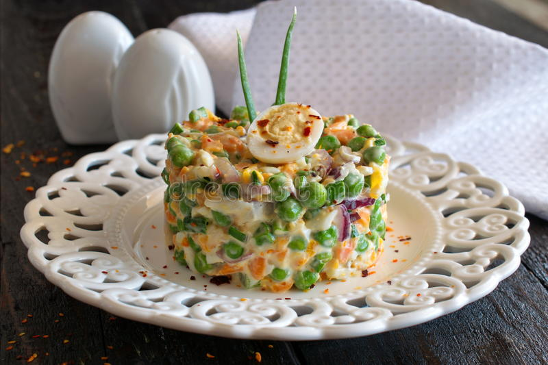 Salad with boiled carrot, peas, eggs,cheese and fresh red onion with yohurt and garlic on a white plate on a wooden stock images