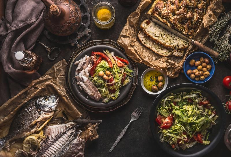 Salad bowl with backed fish and homemade bread on on dark rustic table, top view. Mediterranean lunch or dinner. Healthy food. Salad bowl with backed fish and royalty free stock image