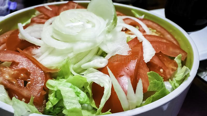 Salad bowl fill with freshly sliced lettuce, tomatoes, and white onions stock photo