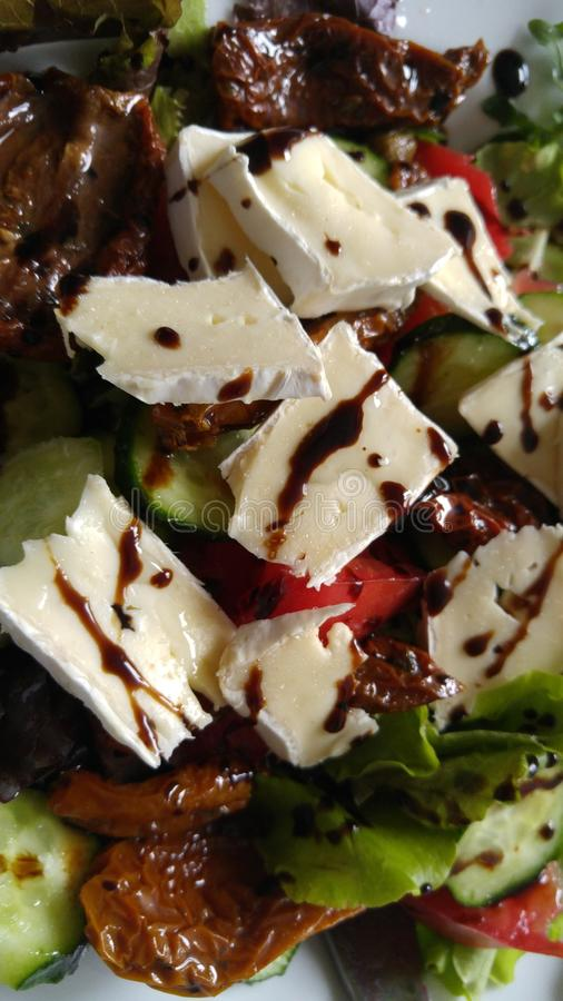 A salad with brie and sun-dried tomatoes royalty free stock images