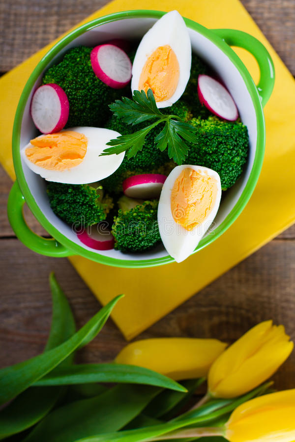 Salad with broccoli. Eggs and radishes in a small bowl on wooden background and tulip bouquet stock image