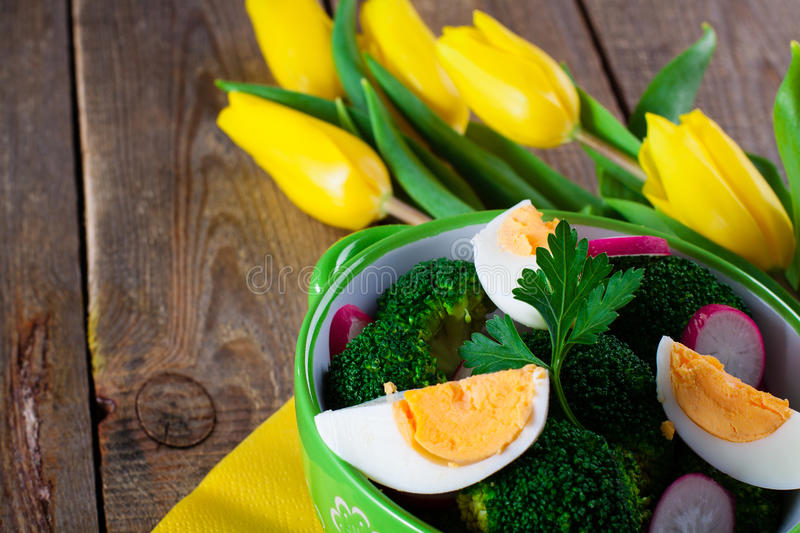 Salad with broccoli. Eggs and radishes in a small bowl on wooden background and tulip bouquet, with copy space royalty free stock photos