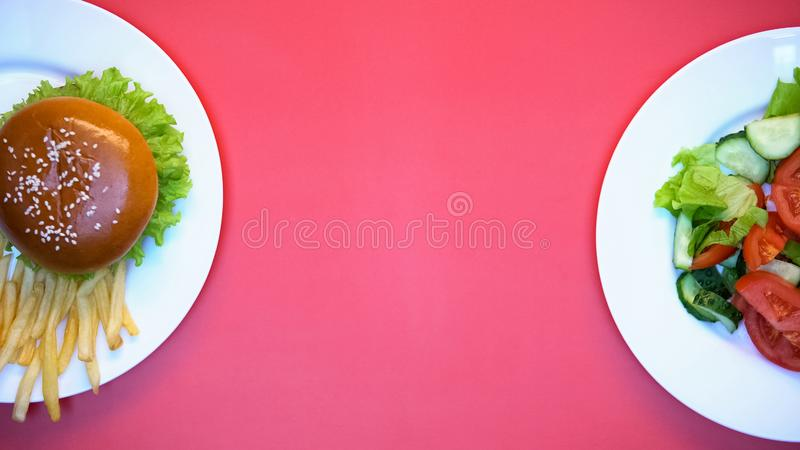 Salad, burger and french fries on white plates on pink background, fast food. Stock photo stock photo