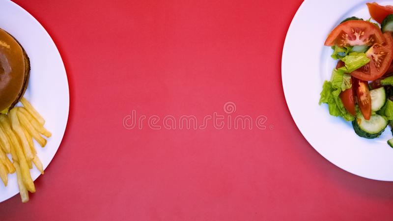 Salad, burger and french fries on white plates on pink background, restaurant. Stock photo stock photography