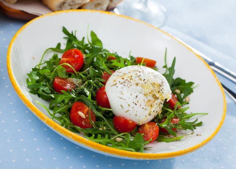 Salad with burrata italian cheese, cherry tomatoes and arugula green leaf stock photos